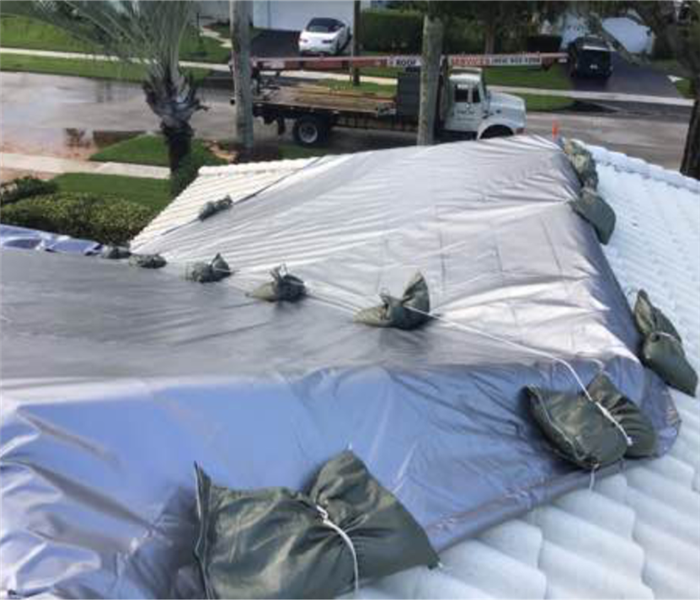 White roof with silver tarp placed and held down by heavy green bags.