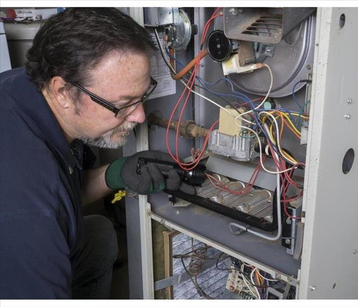 Technician looking over a gas furnace with a flashlight before cleaning it