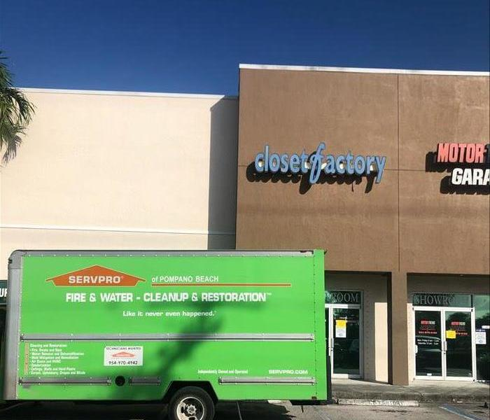 A green SERVPRO truck is seen in front of a business that is being cleaned
