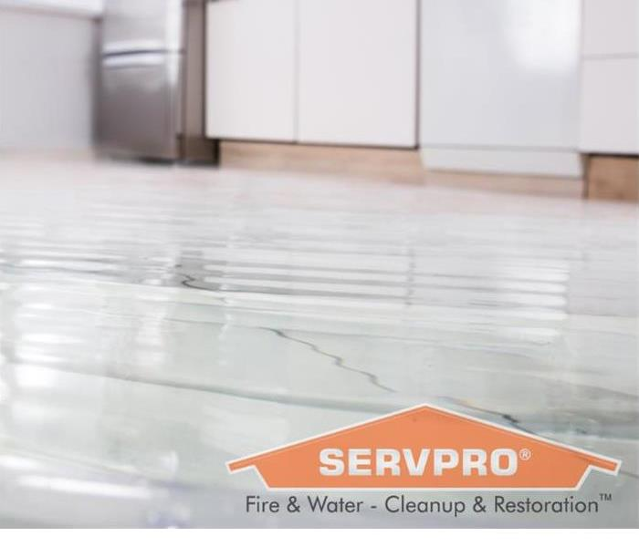 A flooded kitchen floor is shown with a SERVPRO graphic
