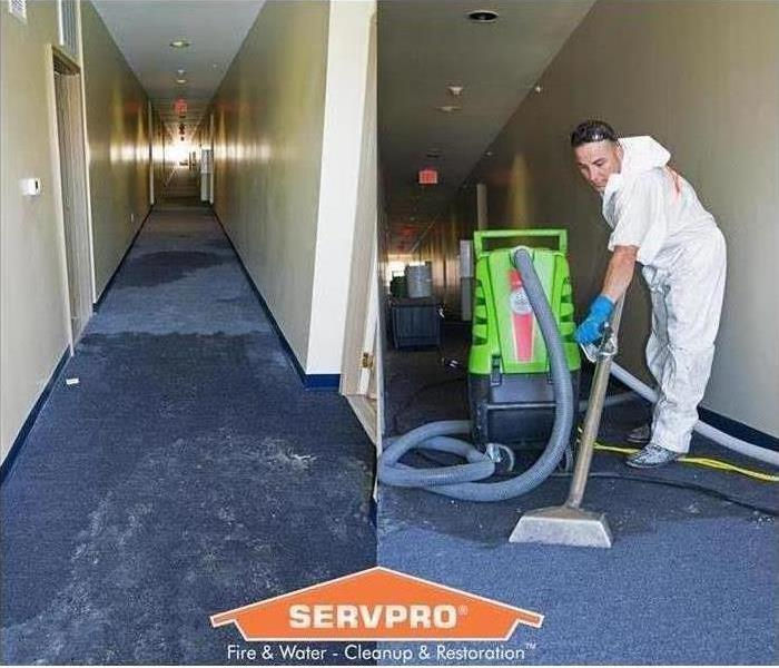 A flooded hallway with a blue floor is shown with a SERVPRO technician cleaning